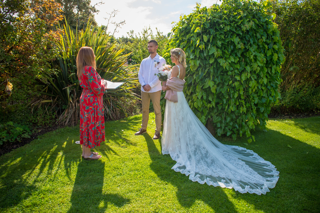 Wedding Photography with Social Distancing during the Covid 19 pandemic. Wedding couple maintaining social distancing with their celebrant