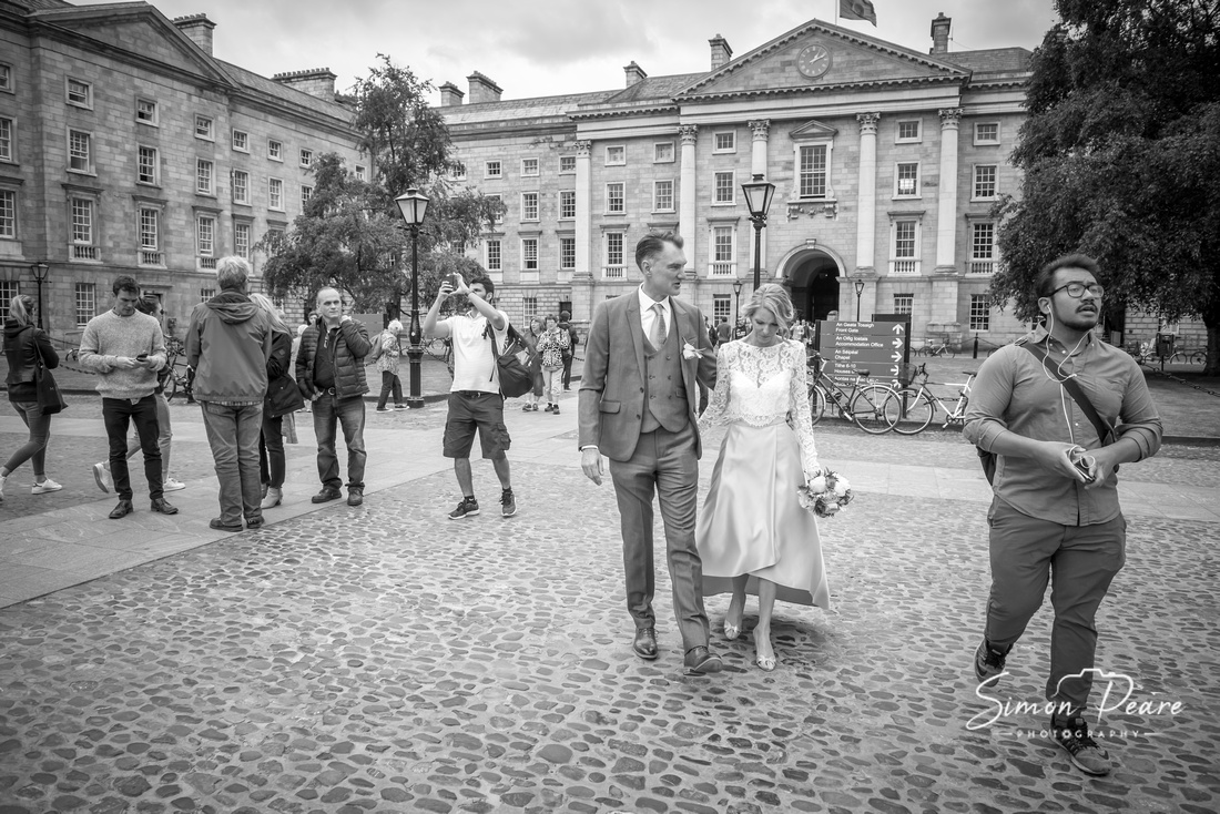 Black and white Natural unposed photograph of Marie & Simon Walking Through Trinity College as tourists take photographs and enjoy the grounds on a summers day. Dublin Wedding Photographer Simon Peare