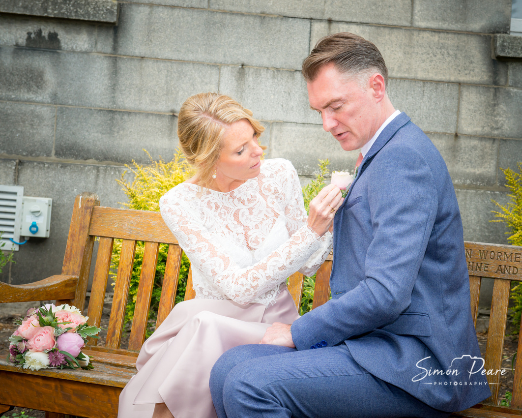 Natural unposed photograph of Marie fixing Simon's flower on a bench in Trinity College. Dublin Wedding Photographer Simon Peare