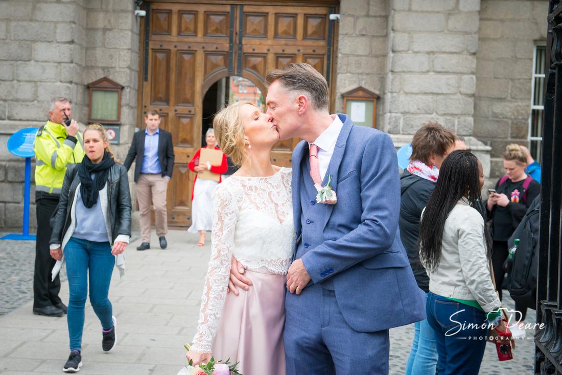 Marie & Simon Wedding Photographs Outsde Trinity College in Dublin City Centre Kissing as everyone else is passing by. Wedding Photographer Simon Peare