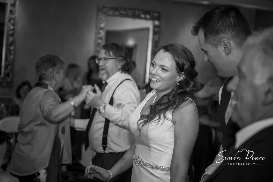 Black and White candid image of Andrea and Michael Dancing the Night Away at Killiney Castle, Dublin. There is a big smile on Andrea's face as Michael looks on surrounded by their guests also dancing. Photograph taken by Dublin Wedding Photographer Simon Peare