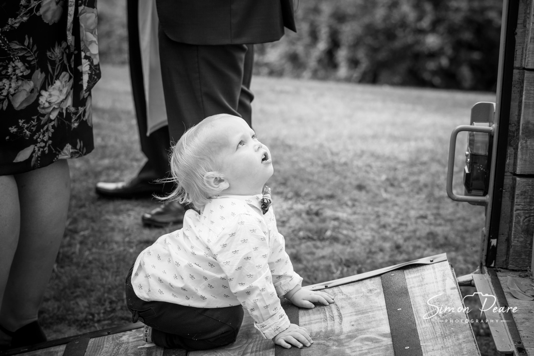Black and White candid shot of a small boy crawling up a wooden ramp to the bar and looking up surrounded by the adults legs at a wedding party. Photograph taken by Dublin Wedding Photographer Simon Peare. Natural Documentary Style Wedding Photography